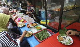 Customers eat nasi uduk, which is Indonesian style steamed rice cooked in coconut milk dish, at street food stall in Jakarta, Indonesia. Tuesday, April 3, 2018. Judges on a popular British cooking show are being ridiculed for ignorance of Asian food after insisting the chicken in a Malaysian contestant's rendang curry should have been crispy. (AP Photo/Tatan Syuflana)