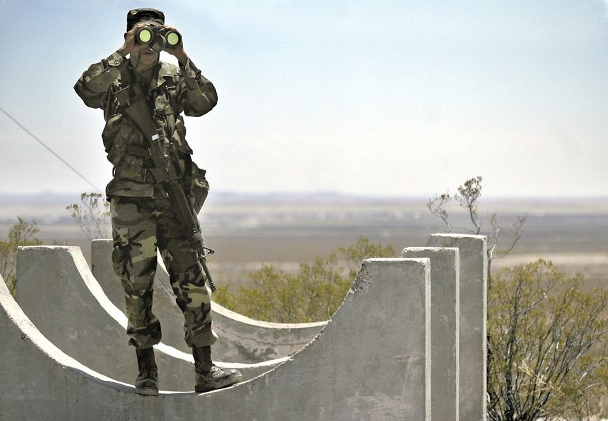 In this June 12, 2006, file photo, Army National Guard Spc. Gustavo Gutierrez, 23, of Las Cruces, N.M., scans the U.S./Mexico border from the top of Radar Hill, near Columbus, N.M. In his threat Tuesday, April 3, 2018, to use the military on the U.S.-Mexico border until his promised wall is built, President Donald Trump again heaped blame on his predecessor, Barack Obama, and congressional Democrats for creating a dangerous and dysfunctional border. (Norm Dettlaff/Las Cruces Sun-News via AP, file)