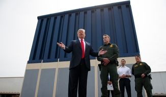 In this March 13, 2018, file photo, President Donald Trump talks with reporters as he reviews border wall prototypes in San Diego. (AP Photo/Evan Vucci, file)