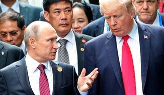 U.S. President Donald Trump (right) and Russia President Vladimir Putin talk during the family photo session at the APEC Summit in Danang on Nov. 11, 2017. (Mikhail Klimentyev, Sputnik, Kremlin Pool Photo via AP) **FILE**
