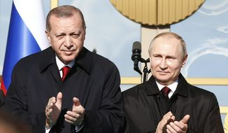 Turkey's President Recep Tayyip Erdogan left, and Russia's President Vladimir Putin, right, applaud during a welcome ceremony at the Presidential Palace in Ankara, Turkey, Tuesday, April 3, 2018. Turkey and Russia have put aside their traditional rivalries and differences on regional issues, to forge closer ties. (AP Photo/Burhan Ozbilici) **FILE**