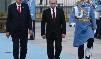 Turkey's President Recep Tayyip Erdogan, left, walks with Russia's President Vladimir Putin, centre, during a welcome ceremony, in Ankara, Turkey, Tuesday, April 3, 2018. (AP Photo/Burhan Ozbilici)