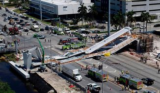 FILE - In this March 15, 2018 file photo, emergency personnel respond after a brand-new pedestrian bridge collapsed onto a highway at Florida International University in Miami. The parents of the youngest victim killed by a collapsed bridge in Miami say they want justice for their daughter, describing her as a selfless teenager who aspired to become a lawyer.  Orlando and Gina Duran said Tuesday, April 3,  there were too many mistakes and oversights in the construction of the Florida International University pedestrian bridge that toppled onto a busy highway March 15, killing their 18-year-old daughter Alexa and five others.   (Pedro Portal/Miami Herald via AP, File)