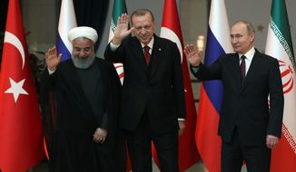 Iranian President Hassan Rouhani, left, Russia's President Vladimir Putin, right, and Turkey's President Recep Tayyip Erdogan wave after a group photo in Ankara, Turkey, Wednesday, April 4, 2018. The leaders of Russia, Iran and Turkey are meeting in the Turkish capital for talks on Syria's future. The leaders are expected to reaffirm their commitment to Syria's territorial integrity and the continuation of local cease-fires when they meet Wednesday. (Tolga Bozoglu/Pool Photo via AP)