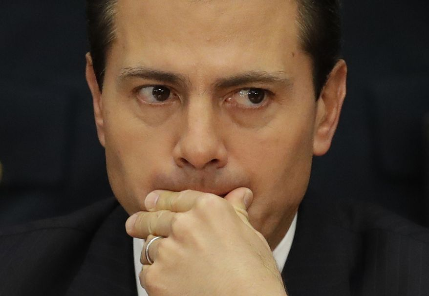 FILE - In this Jan. 9, 2017, file photo, Mexico's President Enrique Pena Nieto listens during an event announcing an accord meant to strengthen the national economy and keep down household costs, in Mexico City. A new poll conducted from Jan. 11-15, shows Pena Nieto's approval rating has fallen to a historic low of 12 percent. (AP Photo/Rebecca Blackwell,File)