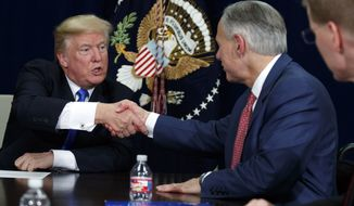 President Donald Trump shakes hands with Texas Gov. Greg Abbott during a briefing on hurricane recovery efforts, Wednesday, Oct. 25, 2017, in Dallas. (AP Photo/Evan Vucci)
