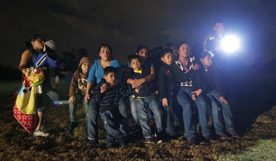 In this June 25, 2014 photo, a group of immigrants from Honduras and El Salvador who crossed the U.S.-Mexico border illegally are stopped in Granjeno, Texas. The epicenter of the recent surge in illegal immigration is a 5-mile slice of deep South Texas that has become a hot spot for migrants, human smugglers and drug cartels. (AP Photo/Eric Gay)