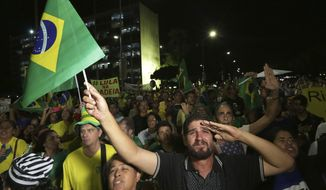 Demonstrators against Brazil's former President Luiz Inacio Lula da Silva watch as Supreme Court justices' votes are made public outside the National Congress in Brasilia, Brazil, Wednesday, April 4, 2018. Brazil's top court is voting on whether da Silva can stay out of prison while appealing a corruption conviction, a decision that could radically alter October's presidential election in Latin America's largest nation. (AP Photo/Eraldo Peres)