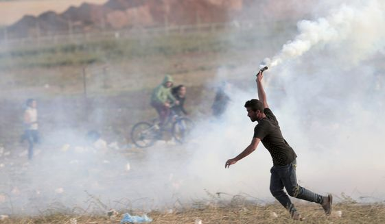 A Palestinian protester prepares to throw teargas back towards Israeli soldiers during clashes with Israeli troops along Gaza's border with Israel, east of Beit Lahiya, Gaza Strip, Wednesday, April 4, 2018. A leading Israel human rights group urged Israeli forces in a rare step Wednesday to disobey open-fire orders unless Gaza protesters pose an imminent threat to soldiers' lives. (AP Photo/Adel Hana)
