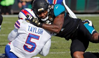 """FILE - In this Jan. 7, 2018, file photo, Jacksonville Jaguars defensive end Yannick Ngakoue, right, draws a penalty by hitting Buffalo Bills quarterback Tyrod Taylor (5) with helmet-to-helmet contact in the first half of an NFL wild-card playoff football game, in Jacksonville, Fla. Bob Costas isn't backing down on his belief that the NFL faces a day of reckoning on the issue of brain injuries, and talks about the one event he wishes he had been able to broadcast on the """"AP Sports Weekly"""" podcast. The NBC and MLB announcer joins co-hosts Jim Litke and Tim Dahlberg to talk about a variety of issues, including the Olympics and how the growing use of analytics has made baseball into a different game than he watched growing up.(AP Photo/Stephen B. Morton, File)"""