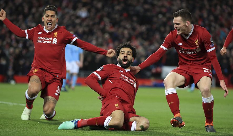 Liverpool's Mohamed Salah, center, celebrates with teammates after scoring his side's first goal of the game during the Champions League quarter final, first leg soccer match between Liverpool and Manchester City at Anfield, Liverpool, England, Wednesday, April 4, 2018. (Peter Byrne/PA via AP)