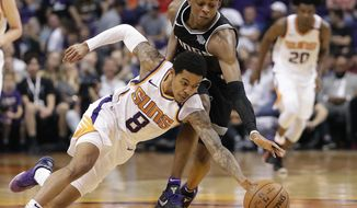 Phoenix Suns guard Tyler Ulis (8) and Sacramento Kings guard De'Aaron Fox (5) chase down the loose ball during the second half of an NBA basketball game Tuesday, April 3, 2018, in Phoenix. (AP Photo/Matt York)