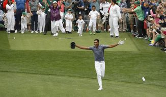 Tony Finau reacts after hitting a hole in one on the seventh home during the par three competition at the Masters golf tournament Wednesday, April 4, 2018, in Augusta, Ga. (AP Photo/Charlie Riedel)