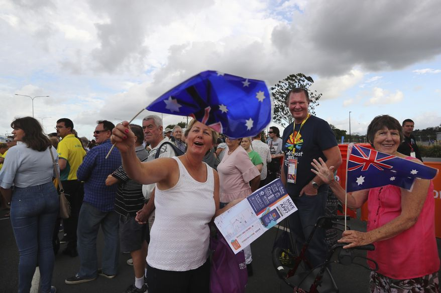Australian women wave their country flags as they wait in a queue to enter the Carrara Stadium for the opening ceremony of the Commonwealth Games in Gold Coast, Australia, Wednesday, April 4, 2018. (AP Photo/Manish Swarup)