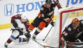 Colorado Avalanche's Matt Nieto, left, tries to score against Anaheim Ducks goaltender Ryan Miller as he is followed by Ducks' Ryan Getzlaf during the third period of an NHL hockey game Sunday, April 1, 2018, in Anaheim, Calif. The Ducks won 4-3 in overtime. (AP Photo/Jae C. Hong)