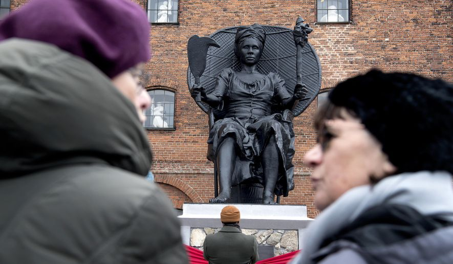 "In this photo taken on Saturday, March 31, 2018 people gather to view the 23-feet sculpture by Danish artist Jeanette Ehlers in collaboration with Virgin Islands artist La Vaughn Belle, dubbed ""I am Queen Mary"" as it is unveiled, in Copenhagen, Denmark.  Two artists have unveiled allegedly Denmark's first public statue of a black woman that questions the Nordic country's colonial past in the Caribbean and its role in slavery. The sculpture depicts a black woman sitting proudly in a wide chair, holding a torch in one hand and a cane cutter in other as a reference to resistance by plantation slaves and their strive for freedom. (Nils Meilvang/Ritzau Scanpix via AP)"