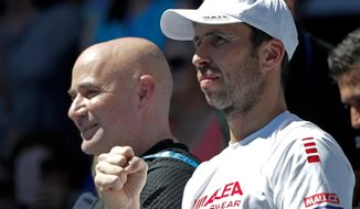 FILE - In this Tuesday, Jan. 16, 2018 file photo, Serbia's Novak Djokovic coaches Radek Stepanek, right, and Andre Agassi, left, watch Djokovic play United States' Donald Young in their first round match at the Australian Open tennis championships in Melbourne, Australia. Novak Djokovic announced on Wednesday April 4, 2018, he has dismissed his coaching team Andre Agassi and Radek Stepanek. It comes after two straight first round defeats at Indian Wells and the Miami Open following a recovery from a long term elbow injury. (AP Photo/Dita Alangkara, file)