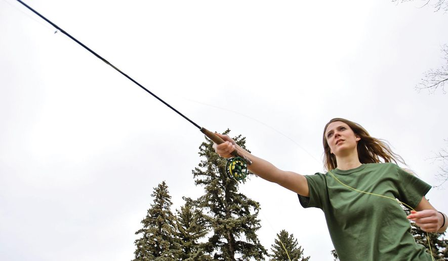 Amy Phillips, vice president of University of Wyoming's Fish N Chicks club, practices casting in Depot Park in Laramie, Wyo., on Saturday, March 24, 2018. (Laramie Boomerang via AP)