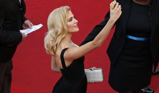 FILE - In this May 21, 2015 file photo, singer Pixie Lott takes a selfie as she arrives for the screening of the film Nie Yinniang (The Assassin) at the 68th international film festival, Cannes, southern France. Film Festival organizers are banning red carpet selfies this year, calling them grotesque and ridiculous. (Benoit Tessier/Pool via AP)