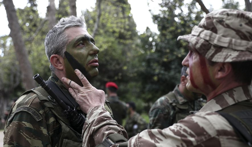 Greece's military personnel prepare themselves ahead of a parade, in Athens, Sunday, March 25, 2018. The parade took place in the Greek capital to commemorate Greek Independence Day, which marks the start of a war of independence in 1821 against the 400-year Ottoman rule. (AP Photo/Yorgos Karahalis)