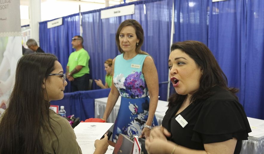 In this March 28, 2018, photo, Roxy Creed, left, speaks to Mandara Spa Operations Manager Lena Andrade about employment opportunities at a job fair in Honolulu. Recently released numbers show Hawaii boasts the United States' lowest jobless rate, at 2.1 percent. But experts say the figure is masking underlying problems. (AP Photo/Audrey McAvoy)