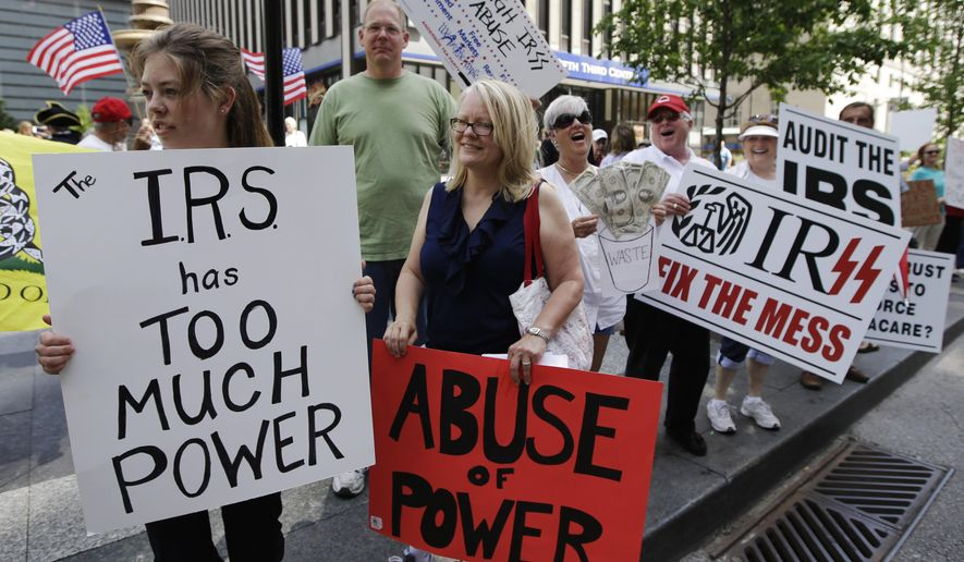 In this May 21, 2013, file photo, tea party activists demonstrate on Fountain Square before marching to the John Weld Peck Federal Building in Cincinnati to protest the Internal Revenue Service's targeting of conservative groups seeking tax-exempt status. On Wednesday, April 4, 2018, a federal judge gave preliminary approval to a $3.5 million settlement of a lawsuit against the IRS over alleged targeting of tea party and other groups. (AP Photo/Al Behrman, File)