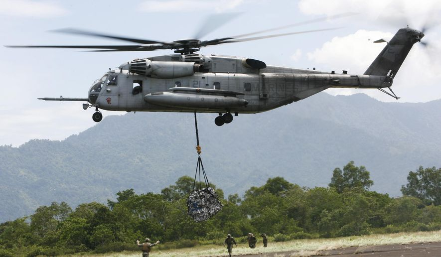FILE - In this Saturday Oct. 10, 2009, file photo, a U.S. military helicopter, the CH-53E Super Stallion, airlifts humanitarian aid to be dropped in affected regions around Pariaman, north of Padang, Indonesia. On Tuesday, April 3, 2018, a CH-53E Super Stallion similar to the one shown went down shortly after 2:30 p.m., during a training mission near El Centro, Calif., a few miles from the U.S.-Mexico border. (AP Photo/Wong Maye-E, File)