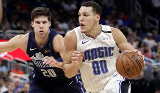 Orlando Magic's Aaron Gordon (00) goes to the basket against Dallas Mavericks' Doug McDermott, left, during the second half of an NBA basketball game Wednesday, April 4, 2018, in Orlando, Fla. (AP Photo/John Raoux)