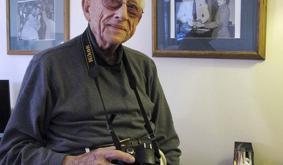 Former Associated Press photographer Gene Herrick poses between two of his most famous pictures at his home in Rocky Mount, Va., on Friday, Feb. 2, 2018. Herrick covered the Rev. Martin Luther King Jr. from his beginnings as a local preacher in Montgomery, Ala., in 1956 to his assassination in Memphis, Tenn., in 1968. (AP Photo/Allen G. Breed)