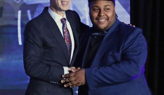 NBA Commissioner Adam Silver, left, poses for photographs with the number 1 overall pick, Artreyo Boyd, at the NBA 2K League draft Wednesday, April 4, 2018, in New York. Launching in 2018, the league will feature the best NBA 2K players in the world and will draft players to compete as unique characters in 5-on-5 play against the other teams in a mix of regular-season games, tournaments and playoffs. (AP Photo/Frank Franklin II)