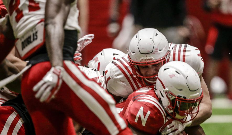 In this April 3, 2018, photo, Nebraska running back Mikale Wilbon, bottom right, is tackled during spring training in Lincoln, Neb. Unlike the trend in the sport of less contact in practices instead of more, Nebraska head coach Scott Frost wants Huskers' practices to be physical to toughen up his team. (AP Photo/Nati Harnik)