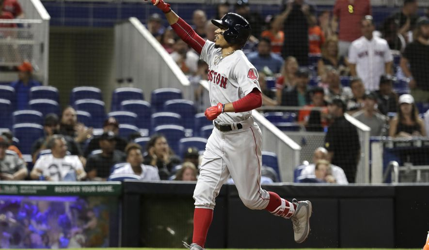 Boston Red Sox's Mookie Betts reacts after crossing home plate with a solo home run in the seventh inning during a baseball game against the Miami Marlins, Monday, April 2, 2018, in Miami. The Red Sox won 7-3. (AP Photo/Lynne Sladky)