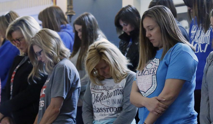 Teachers in the Senate gallery bow their heads for the opening prayer as protestors for increased school funding flood the state Capitol for the third day in Oklahoma City, Wednesday, April 4, 2018. (AP Photo/Sue Ogrocki)