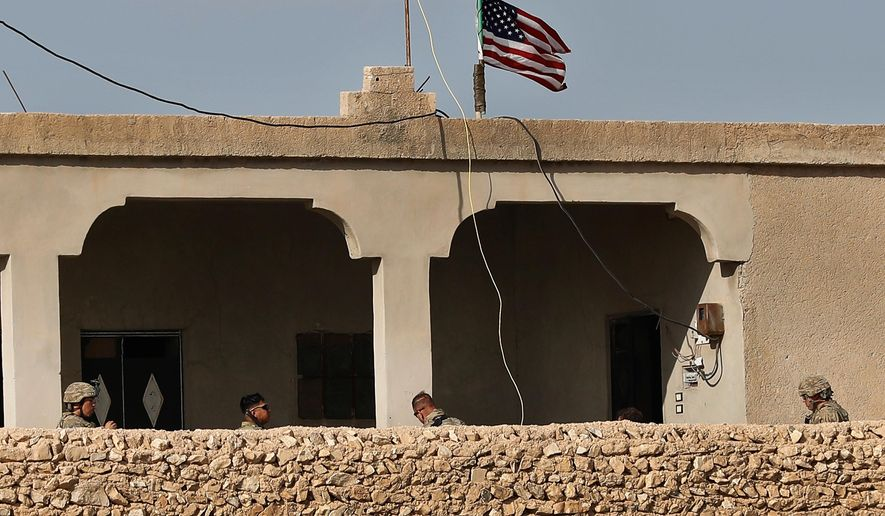 In this Thursday, March 29, 2018 file photo, U.S. soldiers, left, sit in a house turned into an outpost on a road leading to the tense front line between U.S-backed Syrian Manbij Military Council fighters and Turkish-backed fighters, at Halawanji village, north of Manbij town, Syria. (AP Photo/Hussein Malla, File)  **FILE**