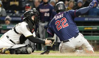 Minnesota Twins' Miguel Sano (22) slides past the attempted tag by Pittsburgh Pirates catcher Francisco Cervelli to score on a double by Logan Morrison off Pirates starting pitcher Ivan Nova during the sixth inning of a baseball game in Pittsburgh, Wednesday, April 4, 2018. (AP Photo/Gene J. Puskar)
