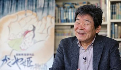 """In this Thursday, Feb. 12, 2015 photo, Japanese animated film director Isao Takahata speaks about his latest film """"The Tale of The Princess Kaguya"""" with its poster during an interview at his office, Studio Ghibli, in suburban Tokyo. The princess laughs and floats in sumie-brush sketches of faint pastel, a lush landscape that animated film director Isao Takahata has painstakingly depicted to relay his gentle message of faith in this world. But his Oscar-nominated work stands as a stylistic challenge to Hollywood's computer-graphics cartoons, where 3D and other digital finesse dominate. Takahata says those terms with a little sarcastic cough. The 79-year-old co-founder of Japan's prestigious animator, Studio Ghibli, instead stuck to a hand-drawn look. (AP Photo/Shizuo Kambayashi)"""
