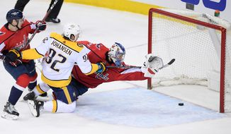 Nashville Predators center Ryan Johansen (92) scores a goal against Washington Capitals goaltender Philipp Grubauer, right, of Germany, during the third period of an NHL hockey game Thursday, April 5, 2018, in Washington. Capitals defenseman Dmitry Orlov is at left. The Predators won 4-3. (AP Photo/Nick Wass)