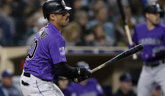 Colorado Rockies' Ian Desmond watches his two-run single against the San Diego Padres during the second inning of a baseball game in San Diego, Wednesday, April 4, 2018. (AP Photo/Alex Gallardo)