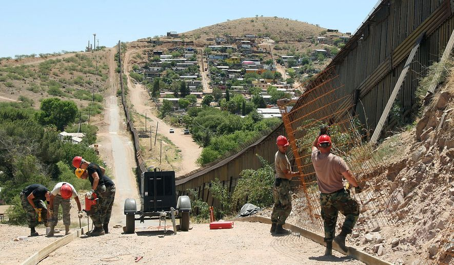 FILE - In this June 20, 2008, file photo, members of the 200th Red Horse Air National Guard Civil Engineering Squadron from Camp Perry in Ohio, including Tech Sgt. David Hughes, right, and Tech Sgt. William Bunker, second from right, work on building a road at the border in Nogales, Ariz. President Donald Trump said April 3, 2018, he wants to use the military to secure the U.S.-Mexico border until his promised border wall is built. (AP Photo/Ross D. Franklin, File)