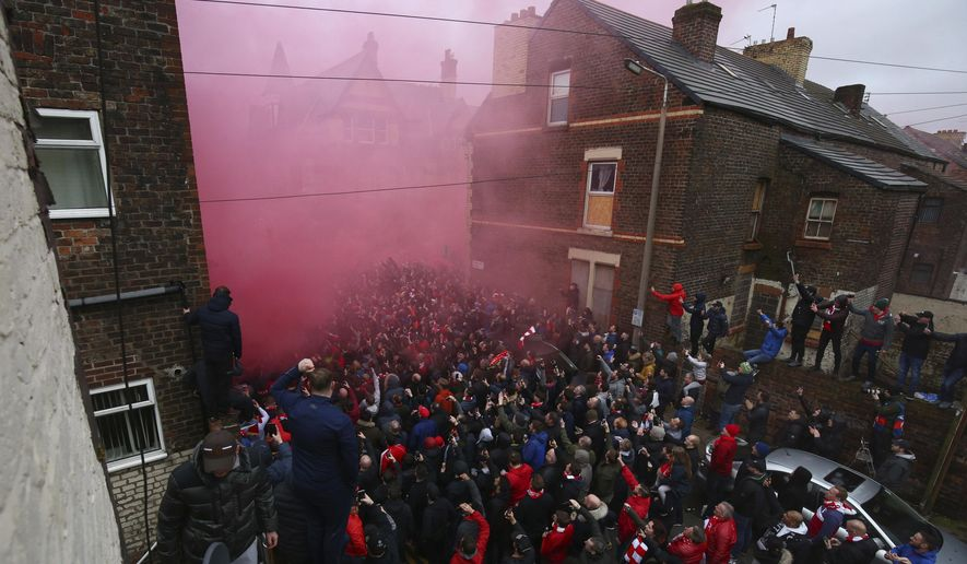 A flare burns as fans try to see the Manchester City team bus as it arrives ahead of the Champions League quarter final first leg soccer match between Liverpool and Manchester City at Anfield stadium in Liverpool, England, Wednesday, April 4, 2018. (AP Photo/Dave Thompson)