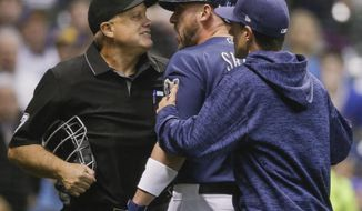 Milwaukee Brewers' Travis Shaw is restrained by manager Craig Counsell after being ejected by home plate umpire Brian O'Nora during the sixth inning of a baseball game against Chicago Cubs on Thursday, April 5, 2018, in Milwaukee. (AP Photo/Tom Lynn)