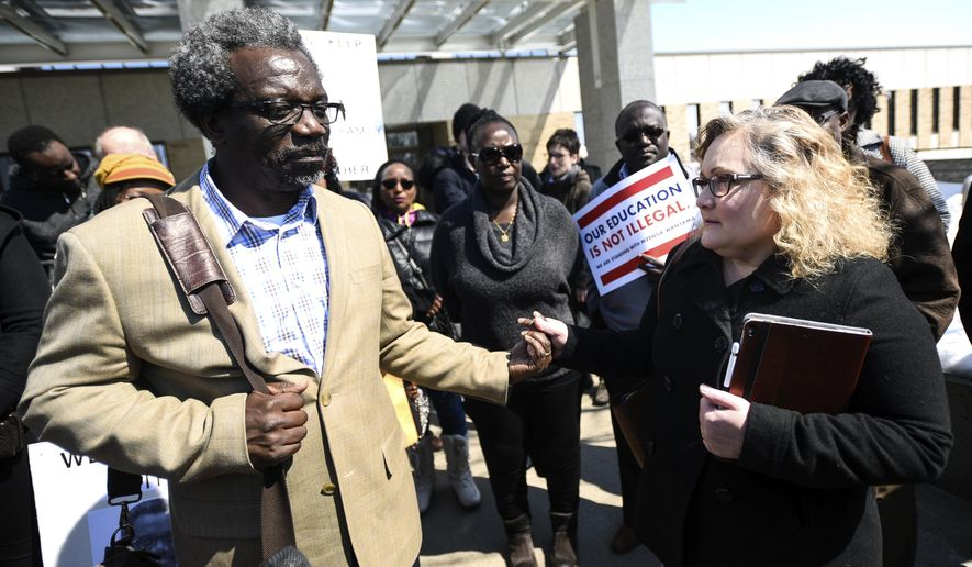 Lori Nixon held the hand of Augsburg Professor Mzenga Wanyama as she expressed her support  outside of the Immigration and Customs Enforcement headquarters Thursday, April 5, 2018, in St. Paul, Minn., after it was announced that Wanyama was ordered to leave the country in 90 days. Nixon attends church with Wanyama at Woodbury Lutheran and is the godmother of his youngest son, a freshman at the University of Minnesota.  (Aaron Lavinsky/Star Tribune via AP)