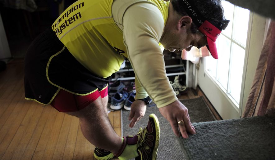 In this Thursday, March 15, 2018, photo, marathon runner John Young, of Salem, Mass., puts on his running shoes before a training run, in Salem. Young was born with dwarfism, but that hasn't stopped him from conquering multiple marathons and triathlons. While most marathoners take about 35,000 steps to reach the finish line, Young uses about 80,000. (AP Photo/Steven Senne)