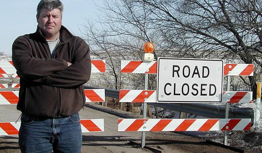 In this undated photo, Saunders County, Neb., Highway Superintendent Steve Mika poses in front of a closed bridge along County Road I, between County Roads 19 and 20. The eastern Nebraska county is nearly caught up on its bridge repair work spanning the last decade. (The Tribune via AP)