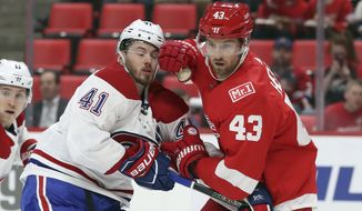 Detroit Red Wings left wing Darren Helm (43) checks Montreal Canadiens left wing Paul Byron (41) during the first period of an NHL hockey game Thursday, April 5, 2018, in Detroit. (AP Photo/Carlos Osorio)