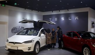 A sales person attends his customers near the Tesla electric vehicles at a showroom in Beijing, Thursday, April 5, 2018. The United States and China, the world's two largest economies, have roiled financial markets and fueled fears of a protracted trade war by threatening tariffs this week on each other's goods. The United States on Tuesday said it would impose 25 percent duties on $50 billion of imports from China, and China quickly retaliated by listing $50 billion of products that it could hit with its own 25 percent tariffs. (AP Photo/Andy Wong)
