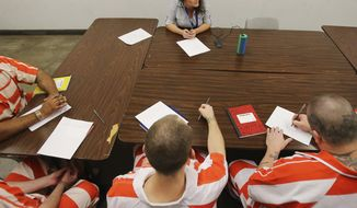 In this March 21, 2018, photo local musician Kayla Ray listens to inmates after playing a song in Waco, Texas. She works with them as part of a prerelease program at the McLennan County Jail.  (Jerry Larson/Waco Tribune-Herald via AP)