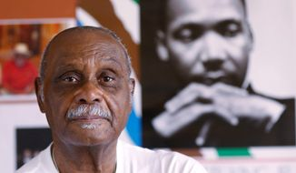 In this March 21, 2018 photo, the Rev. Peter Johnson of Dallas poses for a portrait in front of a poster of Dr. Martin Luther King Jr. in his Oak Cliff office in Dallas. Johnson worked for King all over the South on voter drives since he was a college student. (David Woo/The Dallas Morning News via AP)