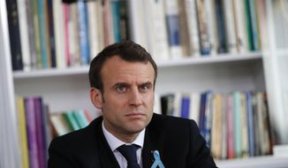 French President Emmanuel Macron listens to hospital staff during a visit at the Rouen hospital, Normandy, Thursday, April 5, 2018. Macron is unveiling a long-awaited autism plan for a country that is shockingly behind the curve on providing basic education and care for people on the autism spectrum. (AP Photo/Christophe Ena, Pool)