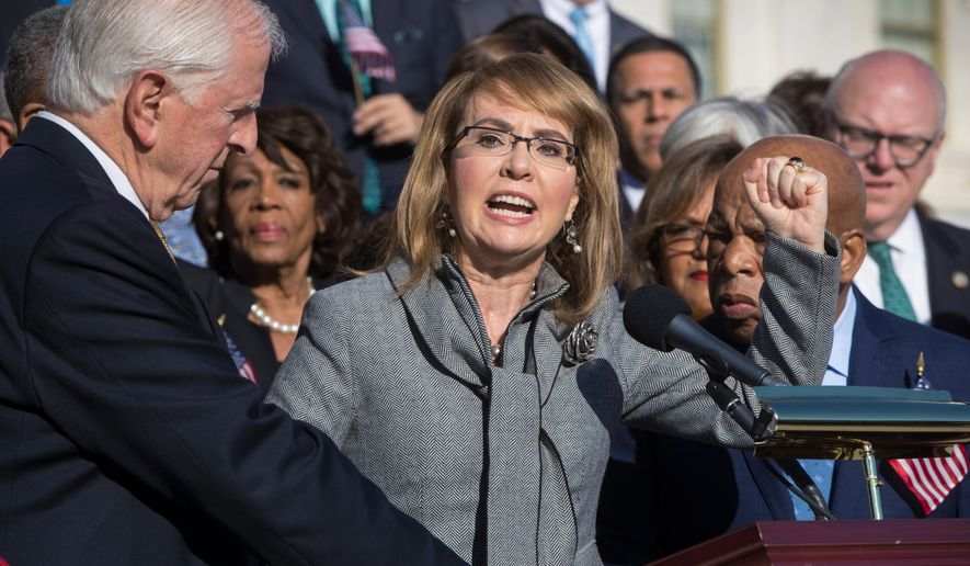 FILE - In this Wednesday, Oct. 4, 2017, file photo, former U.S. Rep. Gabby Giffords, of Arizona, who survived an assassination attempt in 2011, joins other Democrats in a call for action on gun safety legislation on the House steps at the Capitol in Washington. The FBI has released some new photos and video from its investigation of the 2011 shooting in Tucson, Ariz., that left six people dead and 13 injured, including Giffords. (AP Photo/J. Scott Applewhite, File)